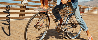 Man and Woman riding on a bike wearing Clarks