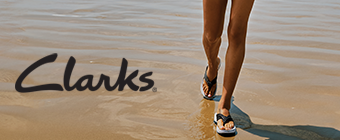Person walking on the beach wearing Clarks