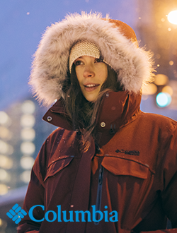 Woman standing outside at dusk with snow falling wearing Columbia