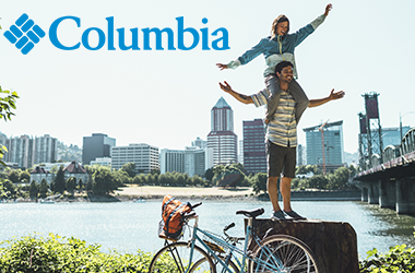 Woman on mans shoulders by the water and a bridge wearing Columbia
