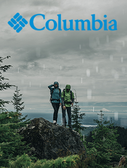 Man and woman standing on rocks in the rain wearing Columbia