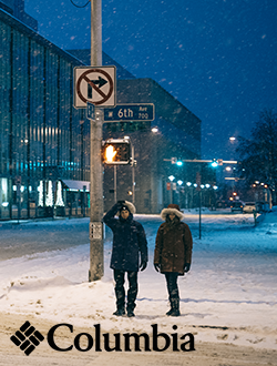 Man and woman walking on a snowy street wearing Columbia