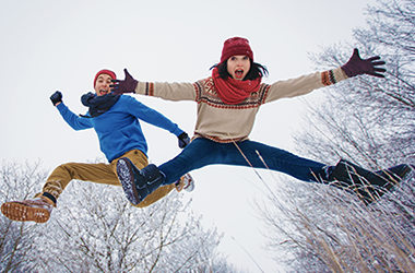 Man and Woman Jumping in Winter