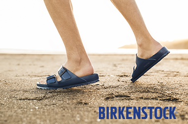 Man wearing Birkenstock sandals wallking on the beach
