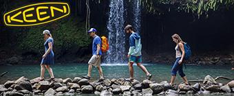 Men and women walking on rocks by waterfall wearing Keen
