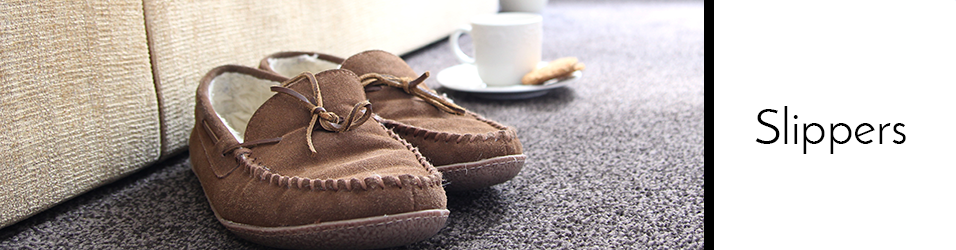 Close up picture of slippers on the floor with a coffee mug on a small plate with a cookie in the background