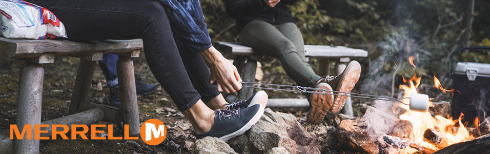 People sitting on a bench near a campfire wearing Merrell shoes