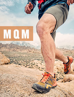 Man and woman walking on mountainside wearing Merrell