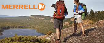Guy and girl standing on mountain over looking water wearing Merrell