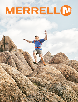 Man jumping from rocks while hiking wearing Merrell