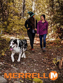 Two women walking in the woods with a dog wearing Merrell