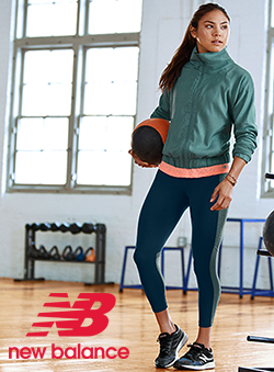 Woman holding weight ball in gym wearing New Balance apparel and sneakers