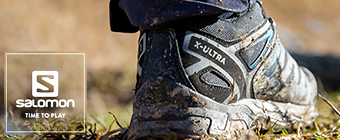 Up close shot of someone wearing Salomon standing in the grass
