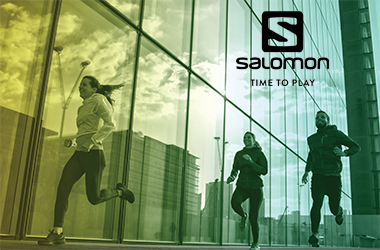 Three people running by a building wearing Salomon