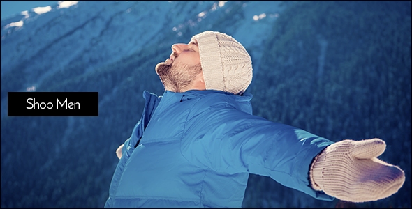 Man standing on a snowy mountain, spreading his arms, looking up and taking in the scenery.