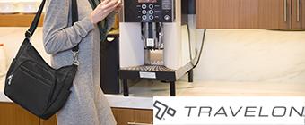 Woman walking away from coffee machine wearing Travelon Anti-Theft Bag.