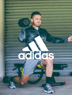 Man in adidas exercise apparel doing lunges with a dumbbell hoisted above his head.