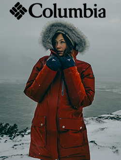 Woman standing on an icy cliff wearing a Columbia jacket