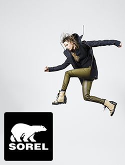 Woman jumping in front of a light grey background wearing Sorel