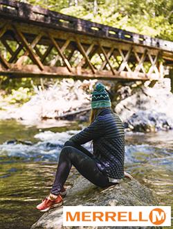 woman sitting on rock near river wearing Merrell