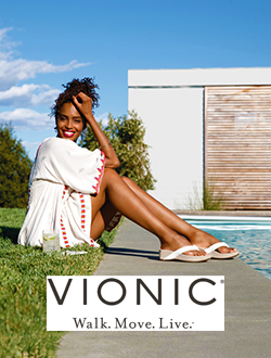 Woman sitting in the grass by a pool wearing Vionic sandals.