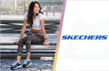 Woman sititng on a bench wearing Skechers