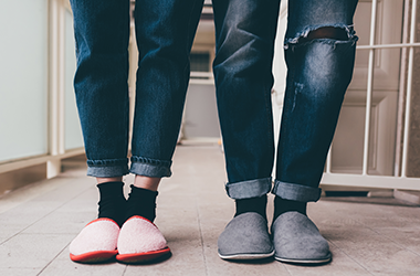 Man and woman standing inside wearing jeans and slippers