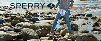 Woman on rocks near the water wearing Sperry