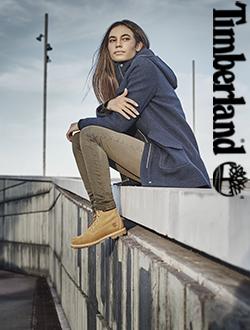 Woman sitting on a ledge wearing Timberland