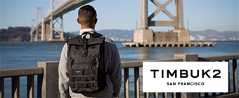 Man standing by the water looking at a bridge wearing Timbuk2