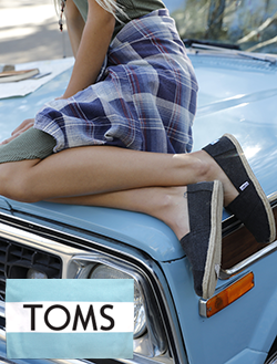 Woman sitting on the hood of a car wearing TOMS