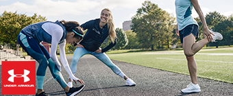 Three women stretching on a track wearing Under Armour