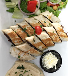 Sizzling marinated Lamb cooked on a vertical grill served in a wrap toasted cut into small wedges with hummus,salad and garlic sauce.