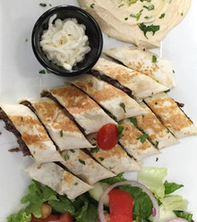 Sizzling marinated Chicken cooked on a vertical grill served in a wrap toasted cut into small wedges with hummus,salad and garlic sauce.