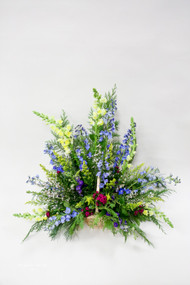 A beautiful Mix of tall flowers arranged in basket for a sympathy piece