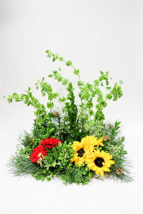 A beautiful simple and unique urn wreath with a touch of vibrant color.