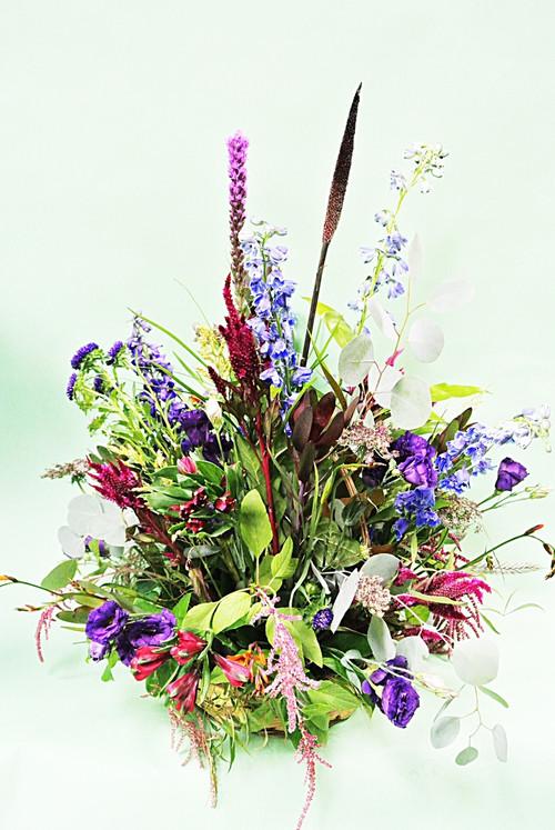 Beautiful mix of fresh flowers arranged in an all around basket wedding decor