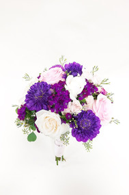 A stunning design of fresh flowers in a bridal bouquet. Designed with love at your Loveland Florist. A Variety of Fresh flowers in pink whites and purples, wrapped in elegance!