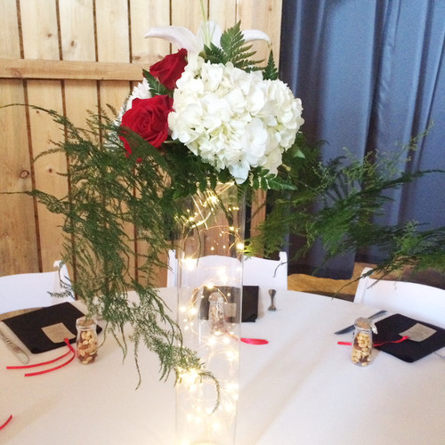 This  centerpiece is desidned locally at your Loveland Florist. With a variety of fresh flowers in reds and whites with greenery falling below. This elegant tall vase includes an accent of lights to complete the unique design.
