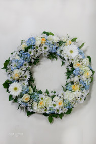 Blue and yellow fresh flower wreath Fresh Flower Holiday Arrangement- Shop locally at Earle's Loveland Flowers and Gifts.