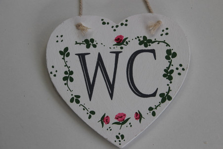 """white wooden """"WC"""" hanging sign"""