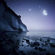 Rising Moon Over Ocean Mountains Against Starry Sky