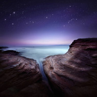 Two Large Rocks In A Sea Against Starry Sky