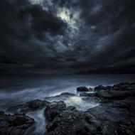Black Rocks Protruding Through Rough Seas And Stormy Clouds Crete Greece