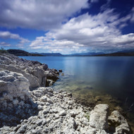 Tranquil Lake With Rocky Shore Against Cloudy Sky Sardinia Italy