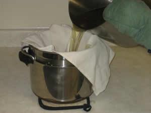 Pour the liquid tallow through a cloth-lined colander into a pot.
