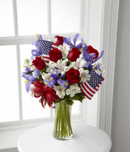 TheUnity Bouquet sparks the hearts of all Americans with its patriotic beauty and dazzling color. Bright red roses mingle with blue iris arranged amongst white Peruvian lilies and assorted greens. Accented with two American Flags and a red, white and