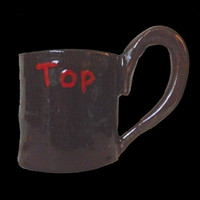 """Handmade clay kinky """"Top"""" clay mug in black with red lettering"""