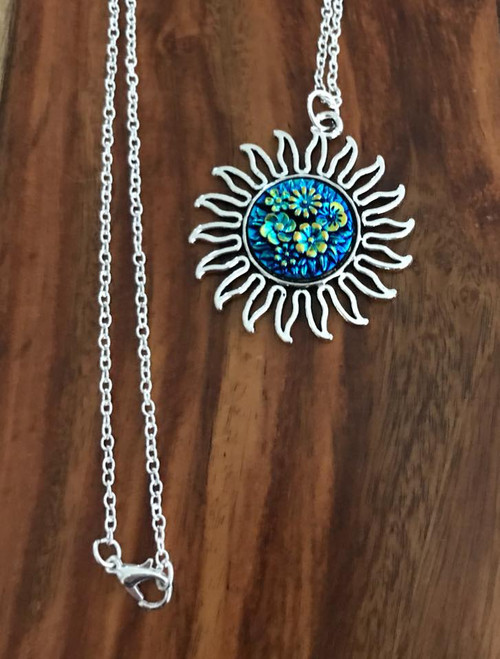 Resell for 12.00 or more Silver tone 30 inch chain  Pewter sun with German acrylic floral blue ab cabachon  Pendant is 1 5/8 inch Style #LBCSN020118g