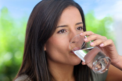 Smiling Woman drinking water from glass
